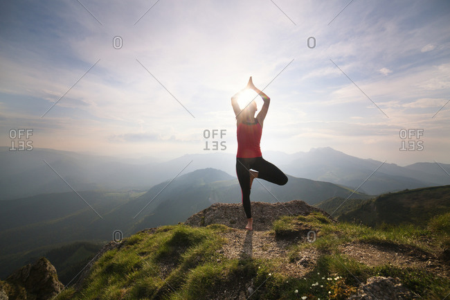 Woman doing yoga on mountain peak