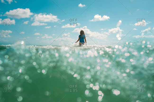 Waterline view of young girl walking into ocean waves