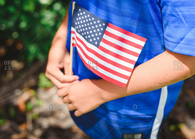 Close up of a young child\'s hands holding an American Flag