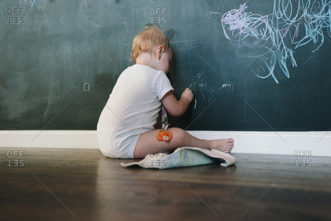 A baby draws on a wall with chalk