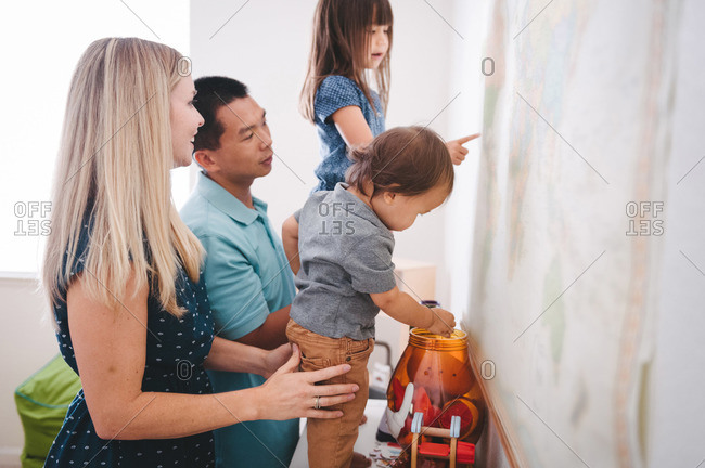 Two children look at a map with their parents