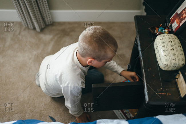 A boy looks through his nightstand