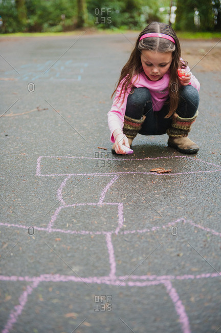 Young girl drawing a hopscotch board on pavement