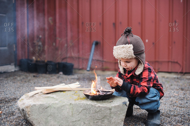 Little boy warming his hands on a campfire in small frying pan on rock