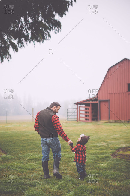 Portrait of father and son wearing matching plaid flannel shirts on misty farm