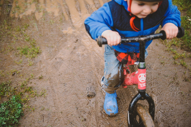 Little boy riding a bicycle on a muddy path