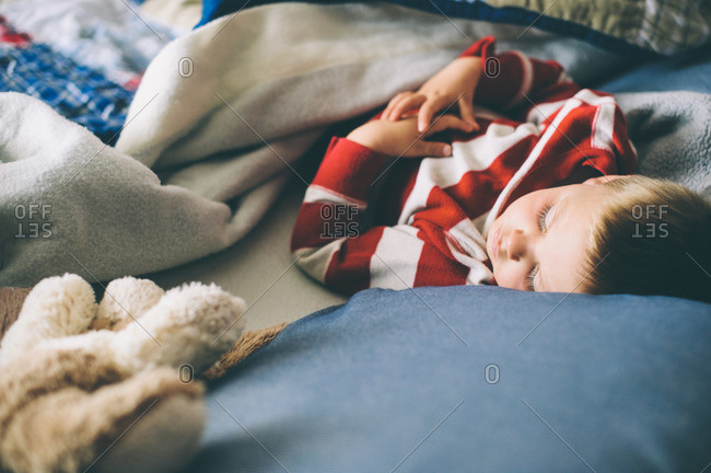 Little boy in striped shirt napping on his bed