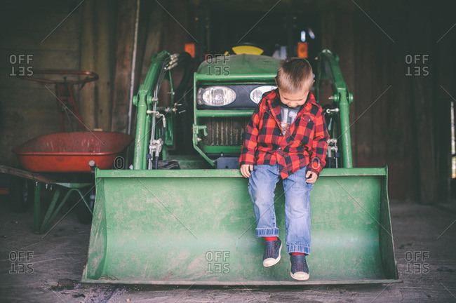 Young boy sitting on the front end loader of a green tractor