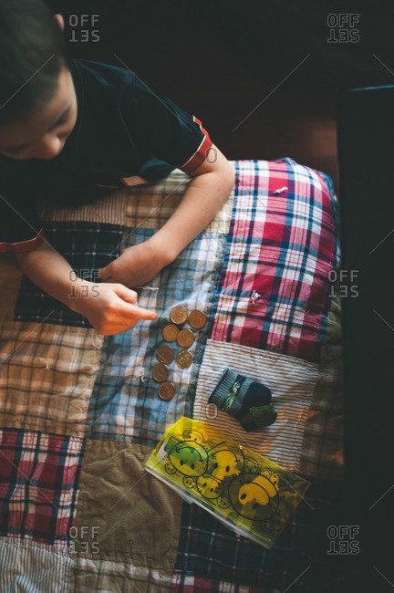 Overhead view of young boy counting money on his bed