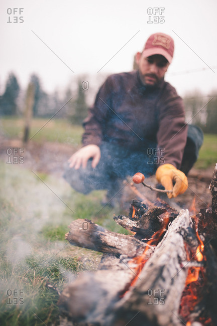 Man cooking a hot dog on stick over campfire