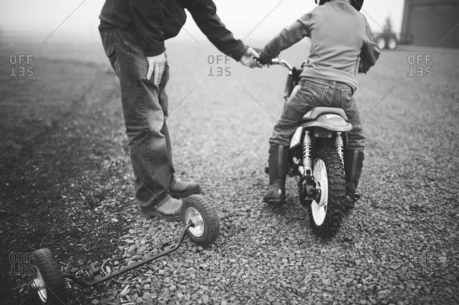 Man helping boy on his youth sized dirt bike