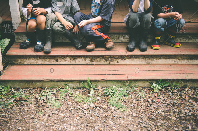 Legs and feet of four children sitting on porch steps
