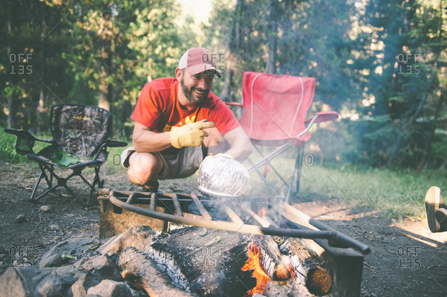 Man making popcorn over campfire