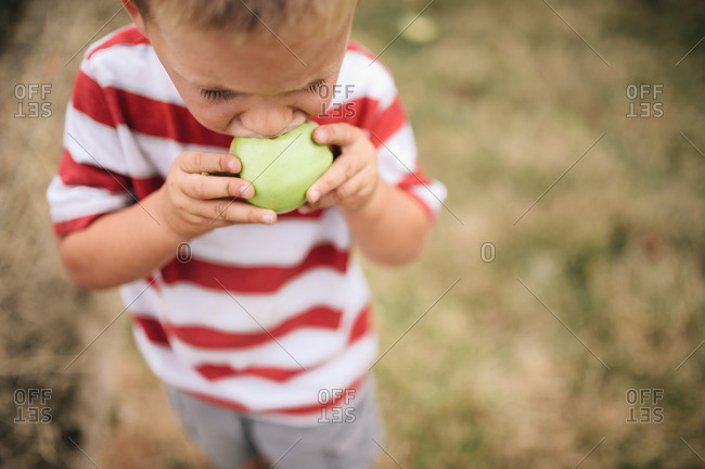 Overhead view of young boy in striped shirt biting an apple