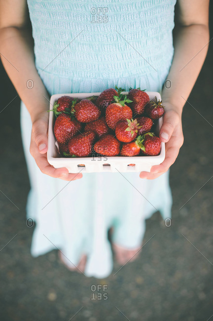 Overhead view of young girl holding a basket of strawberries