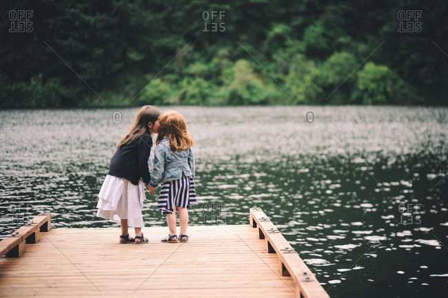 Two affectionate young girls standing on a dock at lake