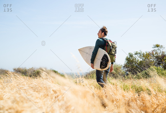 A surfer heads out towards the ocean through dunes
