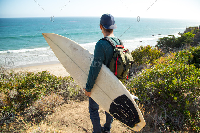 A surfer looks out at the ocean from a dune