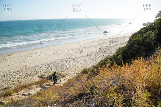 A surfer walks down to the beach
