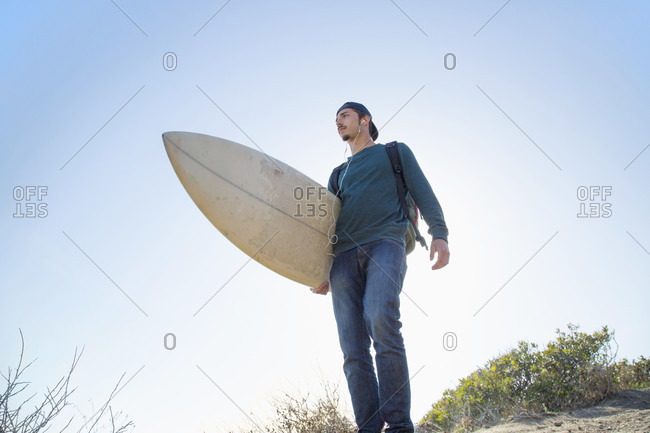 A surfer standing on a sand dune