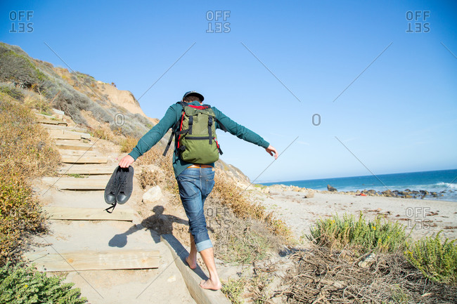 A young man balances on a dune path
