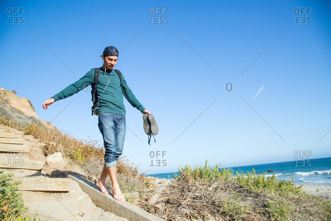 A man balances on a dune path