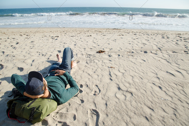 A man rests on a beach