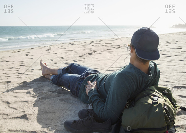 A young man relaxes on the beach