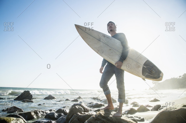 A surfer stands on a rock at the shore
