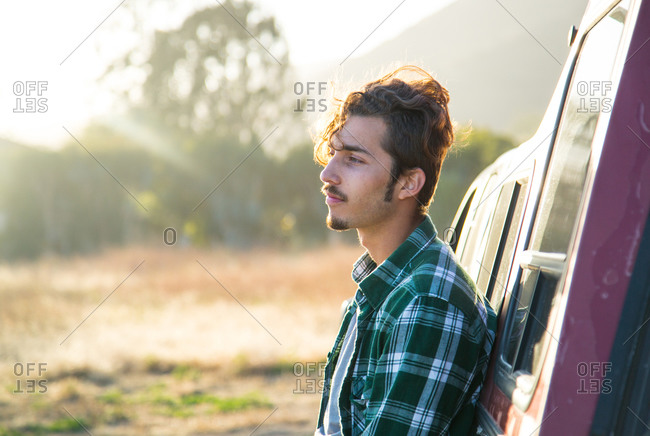 A young man leans against a pickup truck