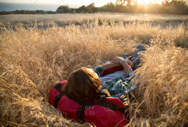 A young man lays down in a grassy field by the ocean