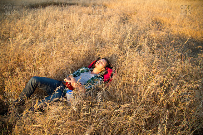 A young man lays down in a grassy field