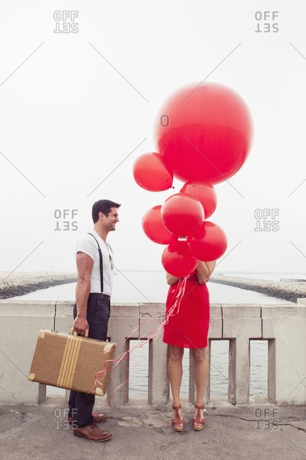 A couple with balloons and a vintage suitcase