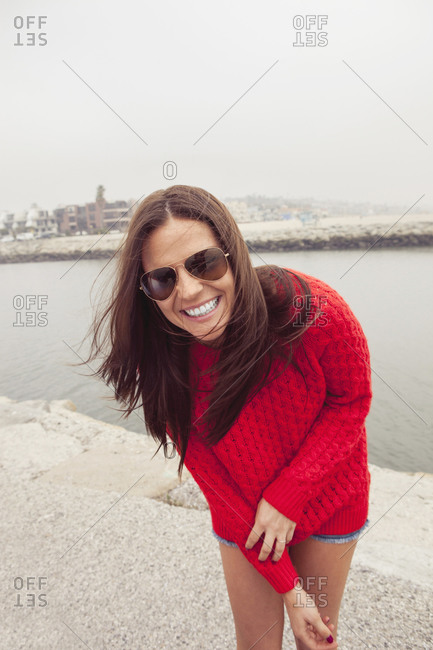 A woman laughs on the edge of a canal