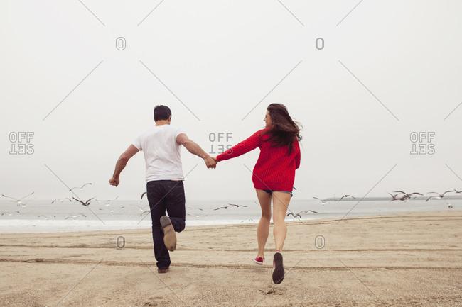 A couple runs with seagulls on a beach