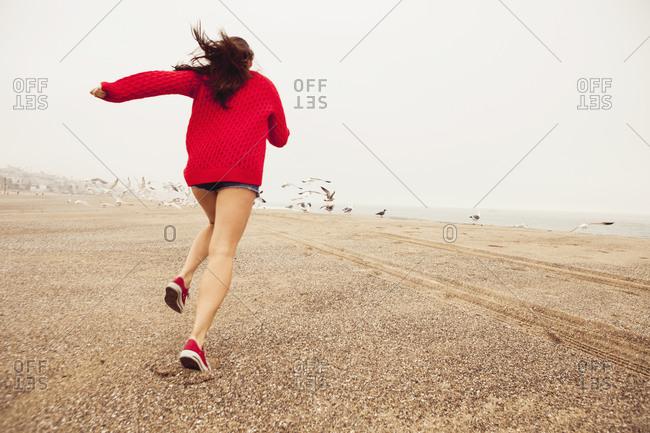 A woman runs towards a flock of seagulls on the beach