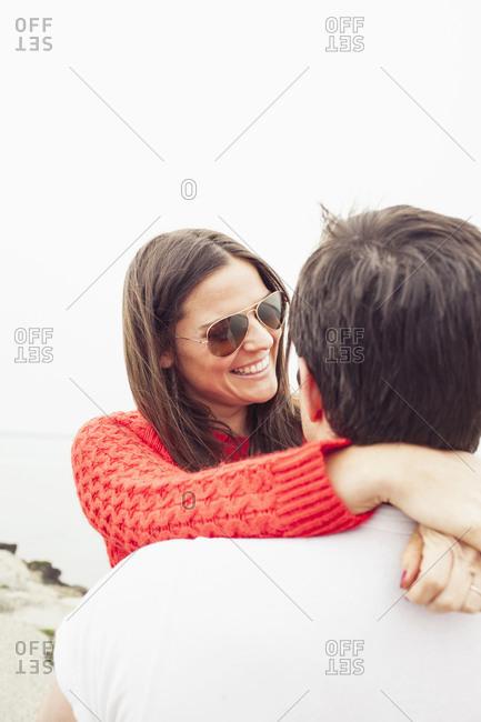 A newly engaged couple hugs on the beach