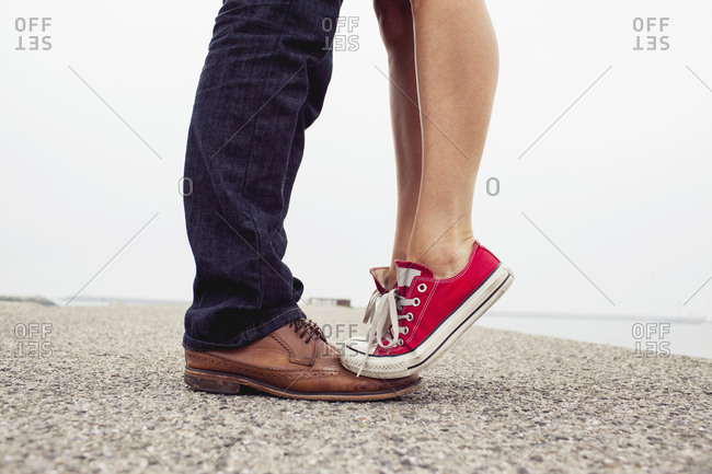 A woman stands on her boyfriend's toes at the shore