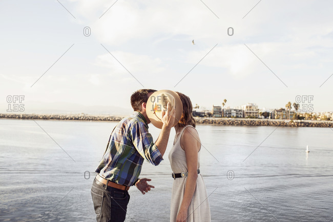 A couple kisses next to the shore in Venice, California