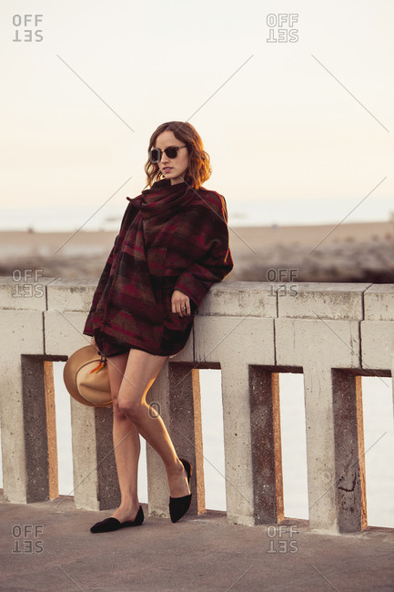 A woman leans against a bridge railing in Venice, California