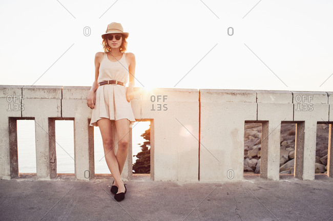A woman leans against a bridge by the ocean in Venice, California