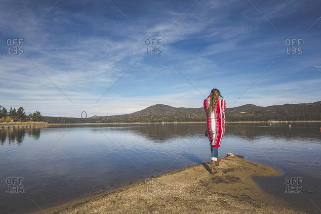 A woman wrapped in a blanket walks towards a lake