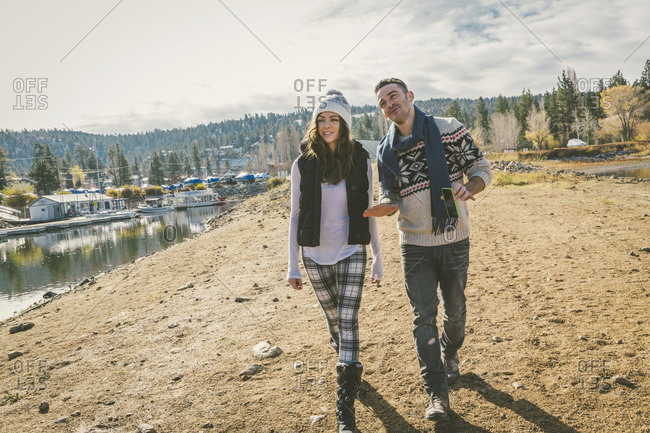 A couple walks along the shore of a mountain lake