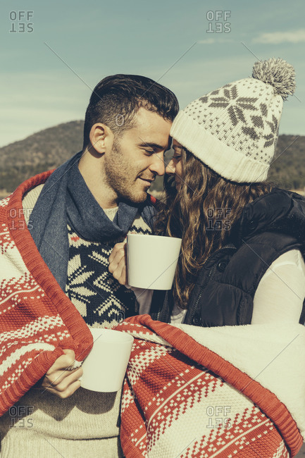 A couple drinks coffee and cuddles in a blanket
