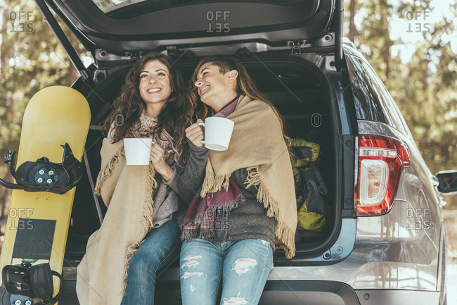 Two women drink coffee while leaning against the trunk of a car