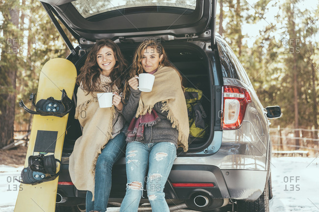 Two women lean against the trunk of a car with a snowboard