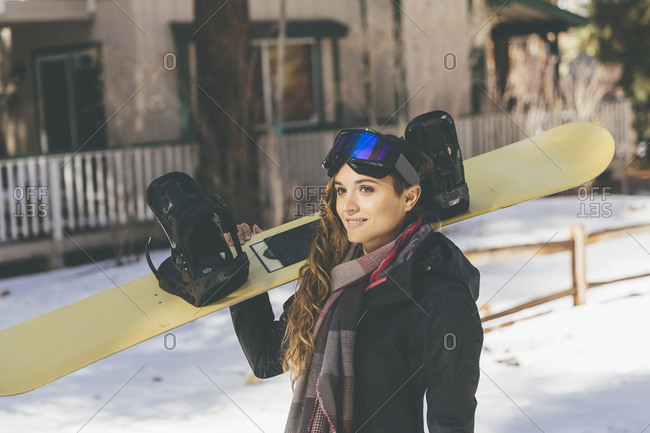 A woman carries her snowboard down a street