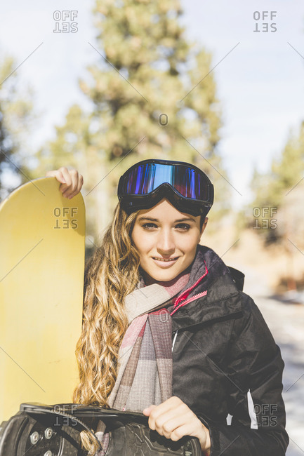 A snowboarder smiles