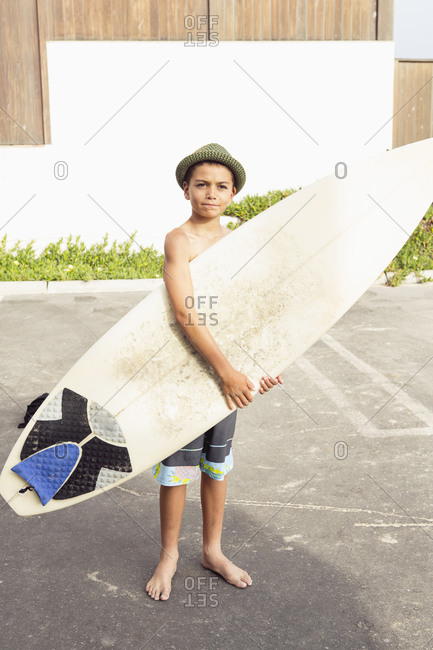 A young boy holds a surfboard in a parking lot