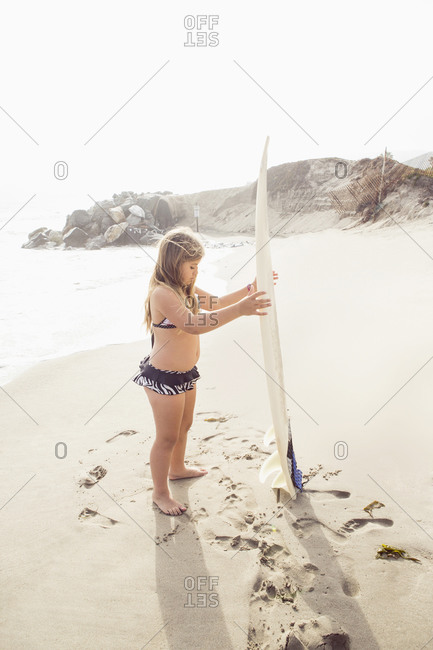 A girl holds a surfboard at the beach